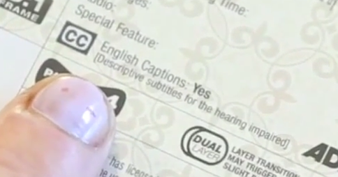 "Finger pointing to the text ""English Captions: Yes [Descriptive subtitles for the hearing impaired]"" on the back of a DVD box"